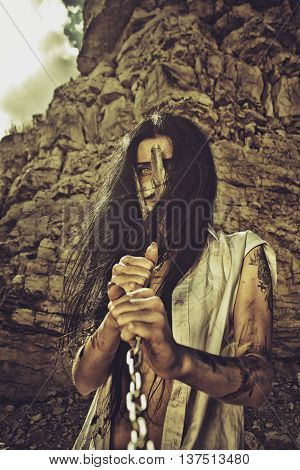 Slave girl in iron mask holding her chains over wasteland of post-apocalyptic world