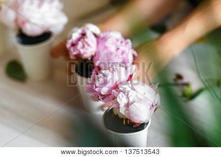 Florist making a bouguet of peonies in kraft paper bag - workshop close up