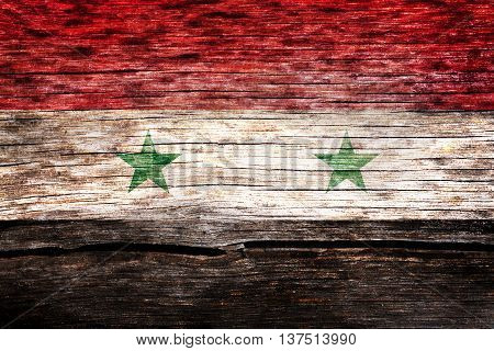 Syria flag painted on the old cracked wood with worn-out paint. Grunge look.
