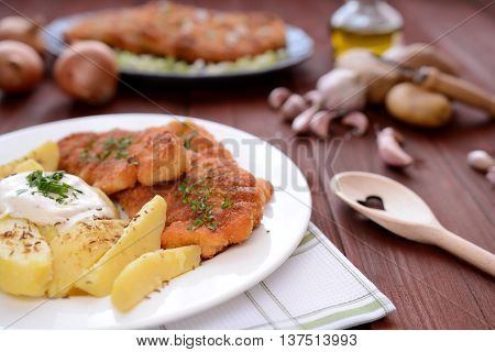 Wiener schnitzel with boiled potatoes on a white plate