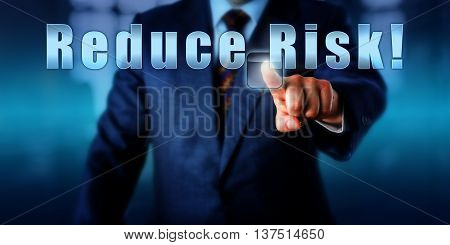Corporate Manager is pressing Reduce Risk! on an interactive touch screen. Business objective concept call to action motivational metaphor and professional advice. Torso shot of man in blue suit.