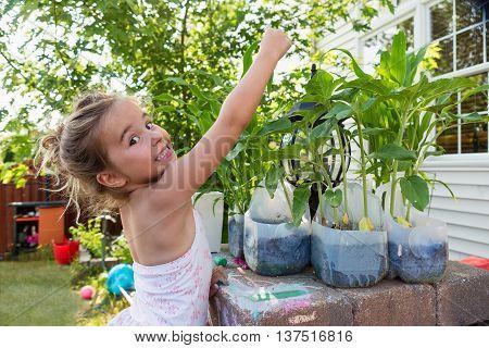 Little Girl Planting Flowers In Plastic Bottles