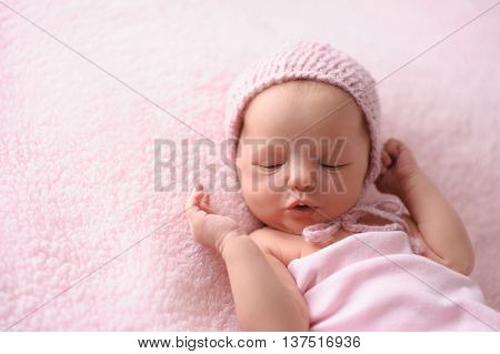 Portrait of a cooing two week old newborn baby girl. She is wearing a knitted bonnet and is lying on a soft fuzzy pink blanket.