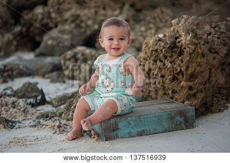 A one year old baby boy smiling and sitting on a wooden crate. Shot outdoors on a beach with rocks in the background.
