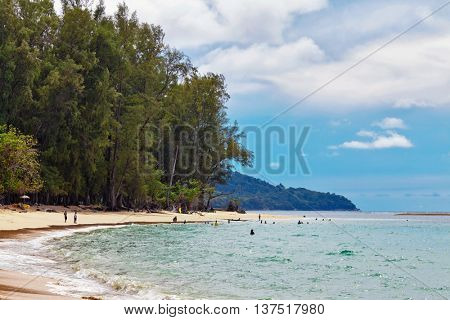 PHUKET, THAILAND- OCTOBER 24, 2014: Thais resting on the Nai Yang beach of Phuket island before sunset. Phuket is located on the west coast of Thailand in the Andaman Sea of the Indian Ocean