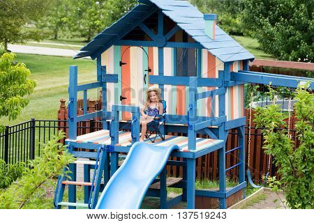 Little Girl In Chair On Outdoor Playset