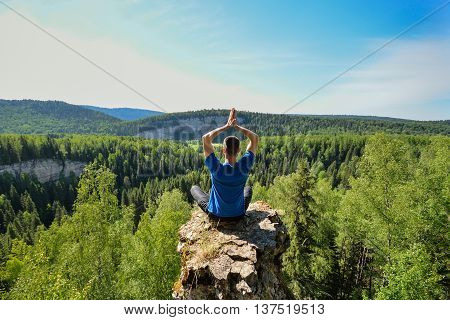 Man sitting on the top of the mountain in yoga pose, leisure in harmony with nature