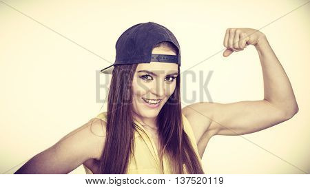 Woman casual style teen girl cap on head showing off muscles biceps. Youth style. Power and strength concept. Studio shot on bright toned image