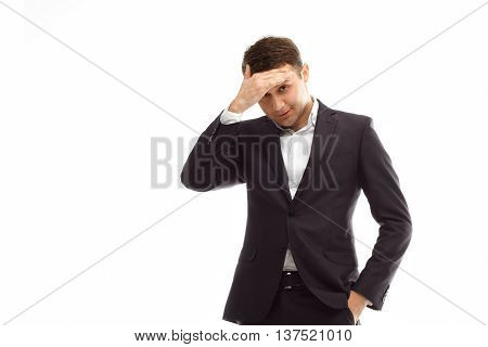 Portrait of handsome businessman wearing black suit put his hand on his forehead isolated on white
