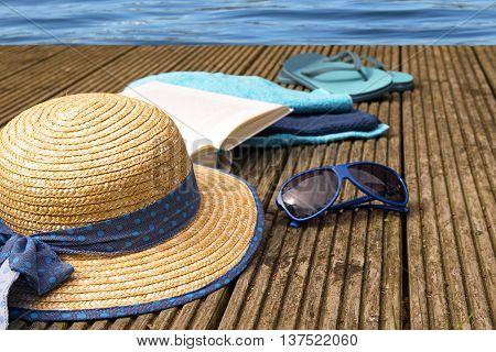 summer vacation accessories for beach holidays as straw hat flip flops, turquoise towels and a book on a wooden bathing jetty right on the water selected focus and narrow depth of field