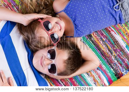 Cute brother and sister in sunglasses laying down on colorful rug while holding each others heads