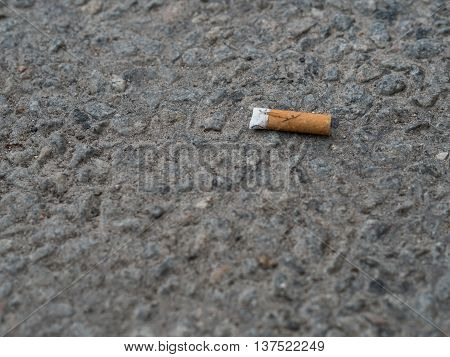 One orange used cigarette on a pavement.