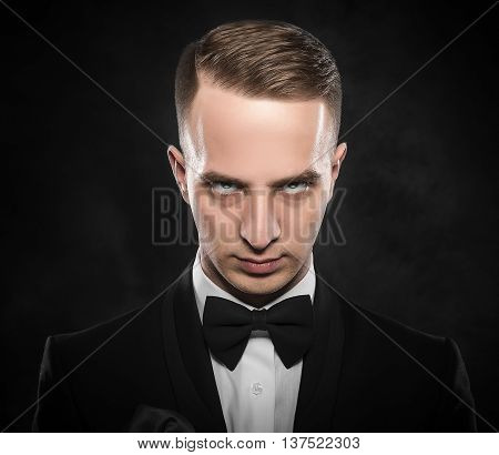 Elegant young man in suit looking frowning on dark background.