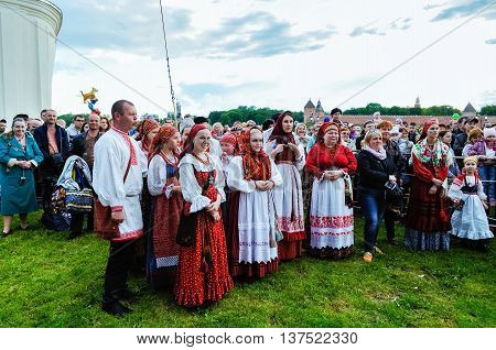 VELIKY NOVGOROD RUSSIA - JUNE 11 2016. Open Air City Day celebration - festive people in traditional Slavic clothes having fun and watching the performance on stage