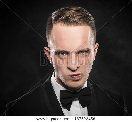Elegant angry young man in suit looking frowning on dark background.