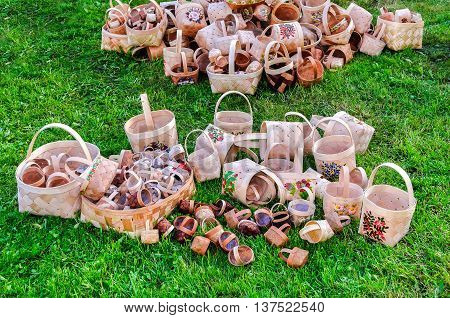 VELIKY NOVGOROD RUSSIA - JUNE 11 2016. Russian wooden hand-woven baskets with patterns lying on the grass in the Craft Fair on City Day