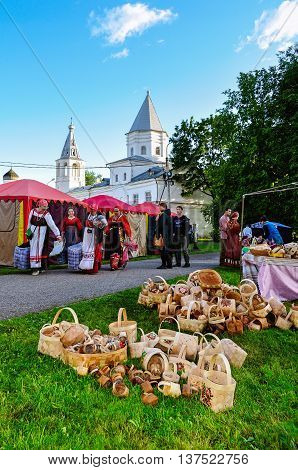 VELIKY NOVGOROD RUSSIA - JUNE 11 2016. Russian fair on City Day Yaroslav courtyard - festive people in traditional Slavic clothes and wooden hand-woven baskets lying on the grass on the foreground