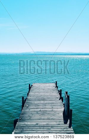 view of a wooden dock over the lagoon in the Albufera de Valencia, in Valencia, Spain