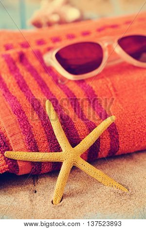 closeup of a yellow starfish on a pile of sand, and a pair of sunglasses on an orange beach towel