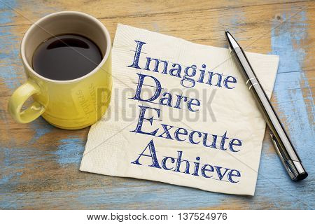 idea acronym (imagine, dare,execute, achieve) - handwriting on a napkin with a cup of espresso coffee