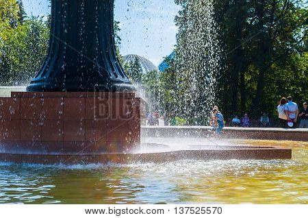 YEKATERINBURG RUSSIA - AUGUST 24 2013. Park summer view - splashing fountain in the city arboretum exhibition and a lot of people having fun in summer nice day in Yekaterinburg Russia