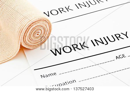 Work Injury claim form with medical bandage on white background.