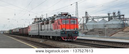 photo of moving locomotive with some tanks and cars. Industry landscape