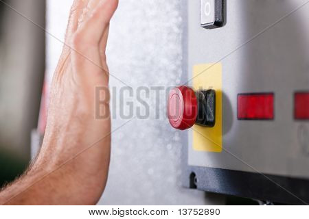 Man is shutting off a machine with the emergency button � probably in a case of danger