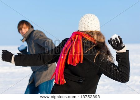 Couple - man and woman - having a snowball fight in winter