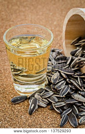 fresh sunflower seeds oil in a glass on wooden background.