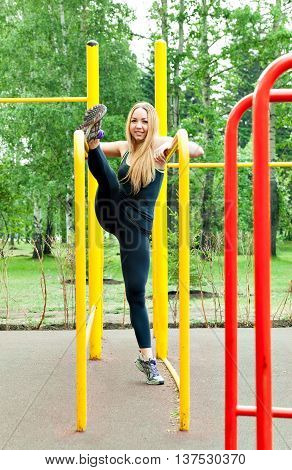 fitness girl on the street gym. Blond fitness woman in sportswear with a perfect body fitness workout on the street to do the exercises on the horizontal bar