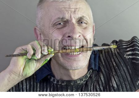 An emotional portrait of a male craftsperson holding a paint brush with his teeth. Studio portrait concept of creativity.