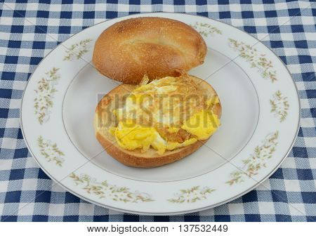 Fried egg bagel breakfast sandwich on white plate on tablecloth