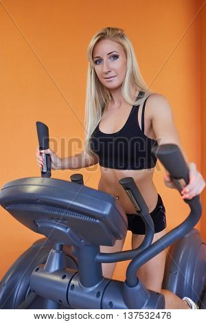 Young sports woman doing exercises on an elliptical trainer in the gym.