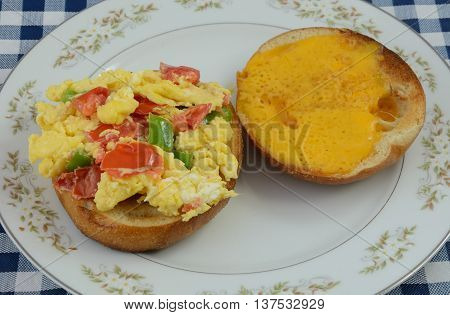 Scrambled egg bagel sandwich with chopped green bell peppers and tomatoes on plate