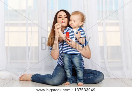 Young mother and small daughter inflate soap bubbles. Mother and daughter dressed in a striped t-shirt. Family joy