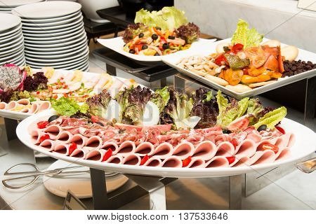 Close-up of cold cuts on white plate.
