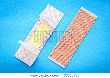 Adhesive bandage plasters set on blue background.