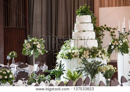 A Wedding cake stands on the decorated table