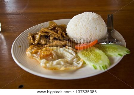 Steamed rice with deep fried pork with garlic served with a sunny-side-up egg