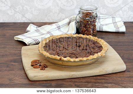 Fresh baked pecan pie with a jar of pecans n the background.