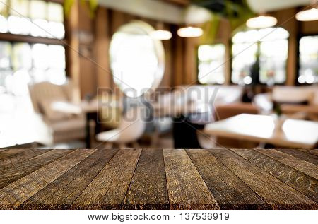 Selected focus empty brown wooden table and Coffee shop blur background with bokeh image. for your photomontage or product display.