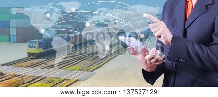 hand presses on world map with digital tabletIndustrial Container Cargo Trains And Truck Of Land Logistic for Logistic Import Export background (Elements of this image furnished by NASA)