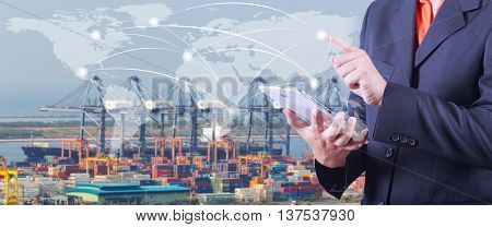 hand presses on world map with digital tablet Industrial Container Cargo freight ship with working crane bridge in shipyard at dusk for Logistic Import Export background (Elements of this image furnished by NASA)