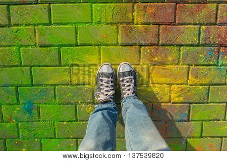 Feet in jeans sneaker on colorful Holi powder background, top view.