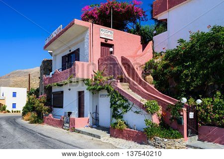 CHORA SFAKION, CRETE, GREECE - JULY 1, 2016: Traditional Greek stone house, decorated with  bougainvillea flowers in Chora Sfakion town at Crete island, Greece
