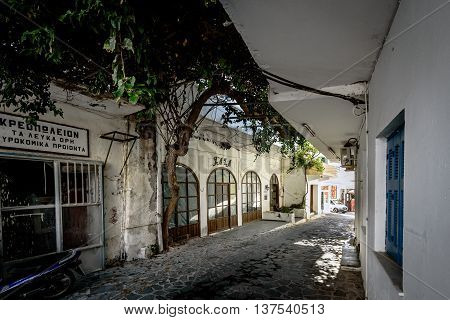 CHORA SFAKION, CRETE, GREECE - JULY 3, 2016: Old dark street with abandoned houses in Chora Sfakion town on Crete island, Greece