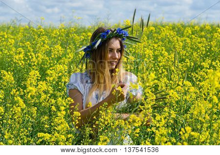 Beautiful girl in wreath of cornflowers on flowering rapeseed field on sunny day
