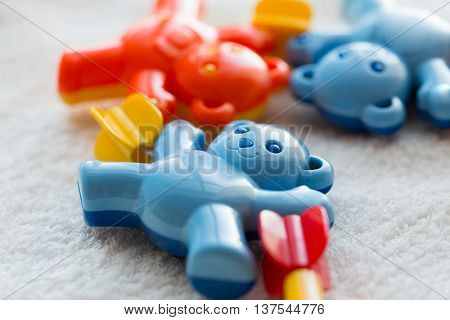 babyhood, childhood, toys and object concept - close up of baby rattle on towel