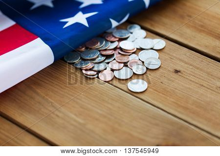 budget, finance, money, crisis and nationalism concept - close up of american flag and cent coins